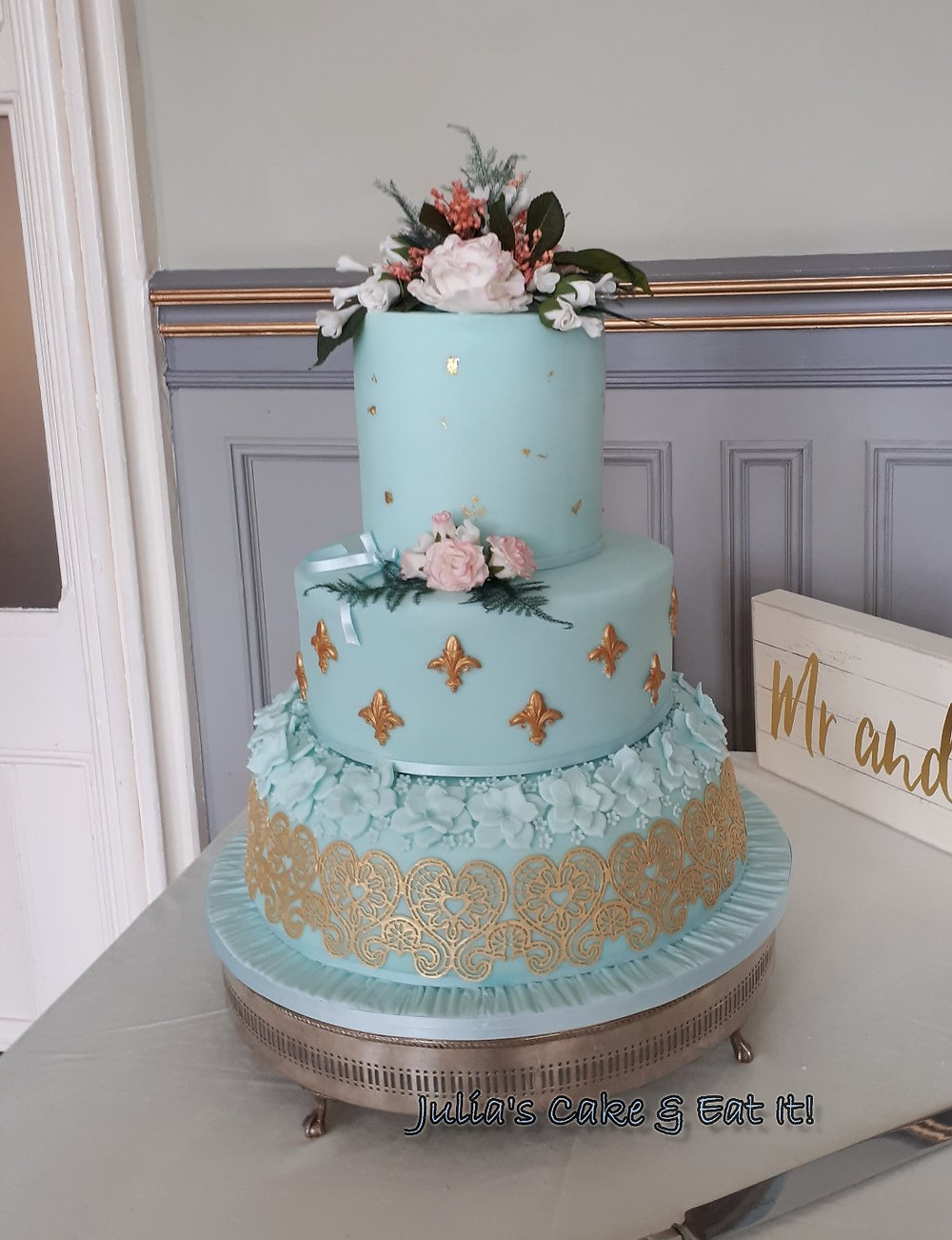 Beautiful pale turquoise three tier wedding cake with edible gold lace an hand mde sugar flowers