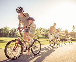 Happy family is riding bikes outdoors an