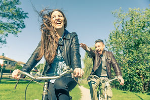 Couple riding on bicycles  and having fu