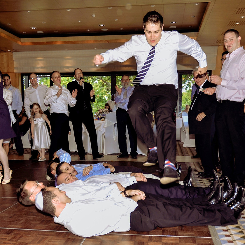 Man jumping over other men at wedding