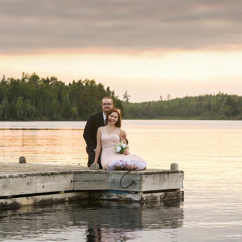 Bride and Groom sitting on dock in lake