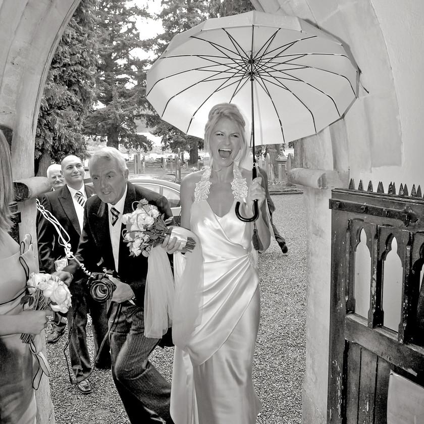 Bride  holding umbrella with groomsmen in background