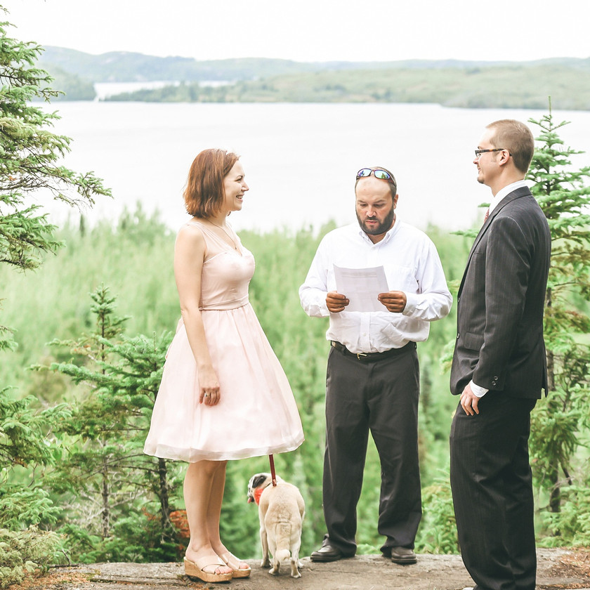 Bride and Groom getting married with dog on leash in the forest