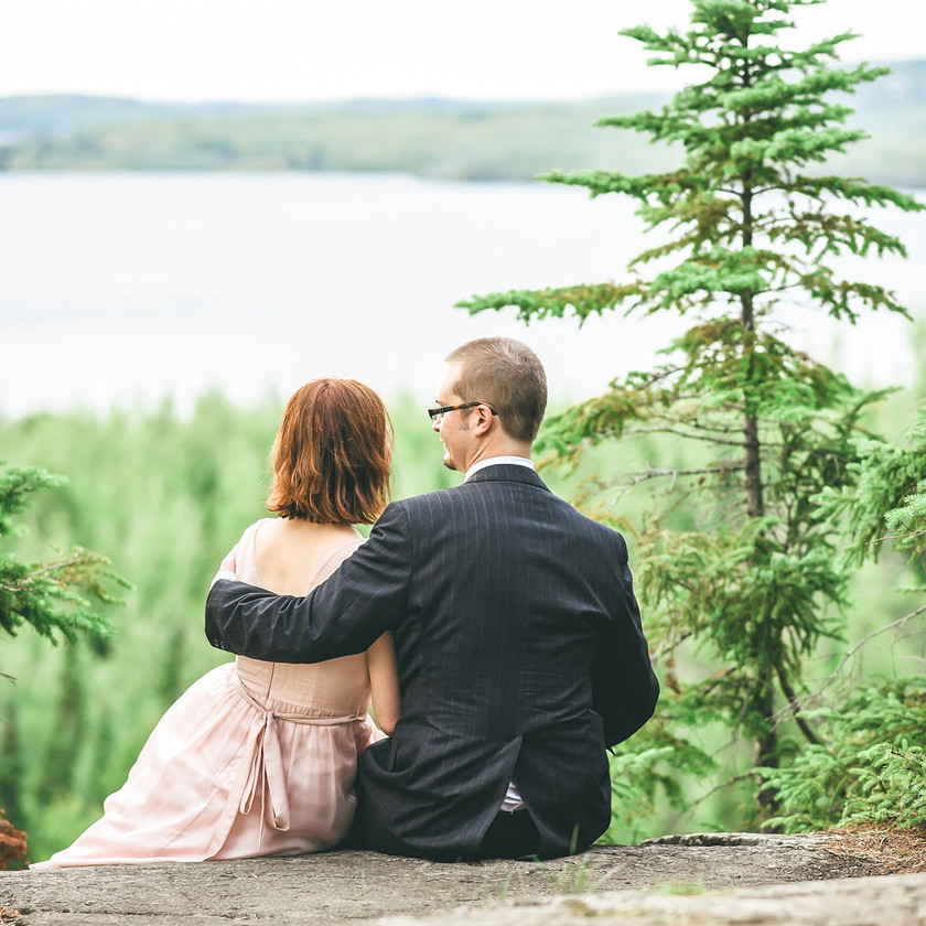 Groom with arm around Bride in the forest