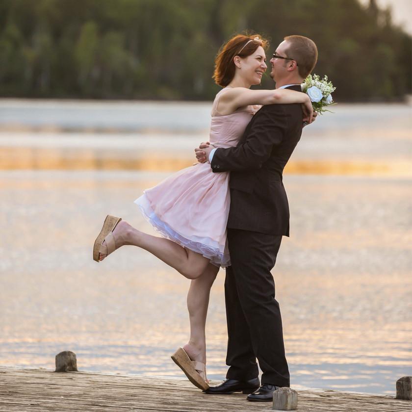 Bride and Groom hugging on dock in lake