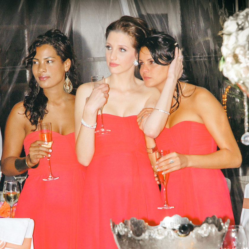 Three bridesmaids in coral dresses