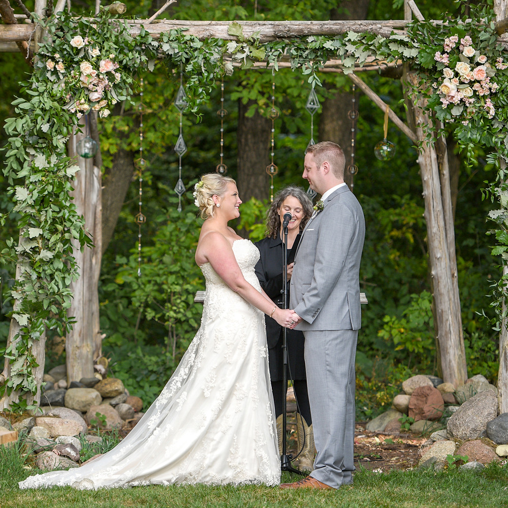 Wedding couple holding hands under a flower filled wedding arch with the minister pronouncing them married