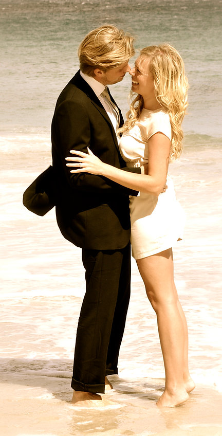 Wedding couple standing in the ocean barefoot arm i arm looking into each others eyes