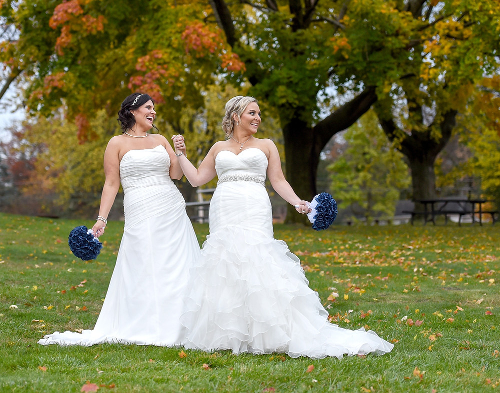 Two brides in white wedding gowns holding hands
