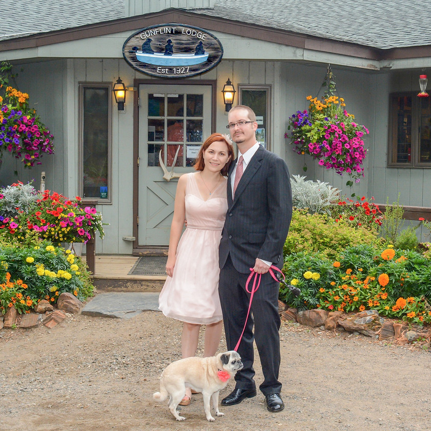 Bride and Groom with dog on leash in front of Gunflint Lodge