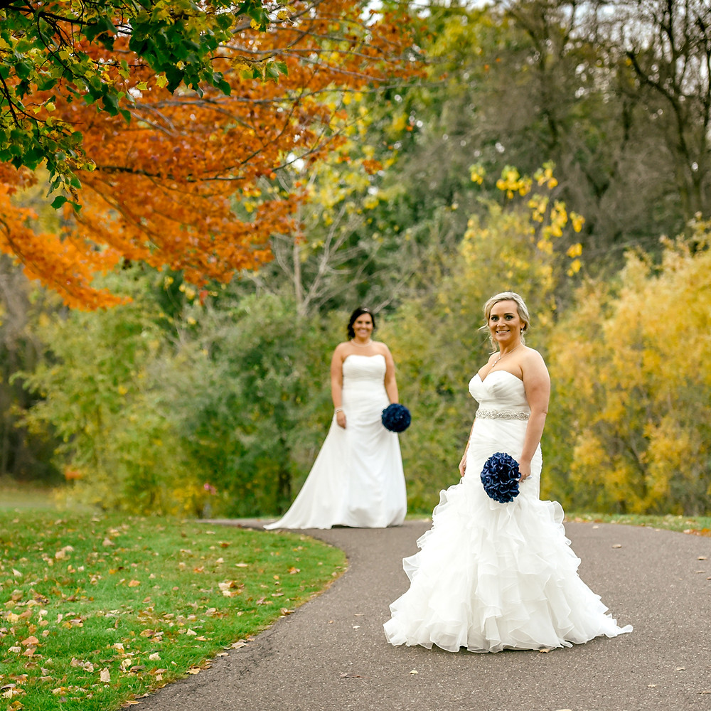 Two brides in white dresses with navy blue flower bouquets surrounded by fall colors