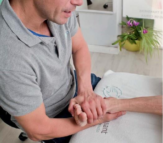 Un fisioterapeuta de Mans de Sant trata con fisioterapia un esguince de tobillo en Sant Cugat