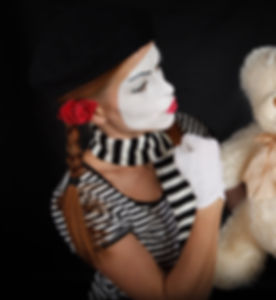 Mime comedian playing with teddy bear, i