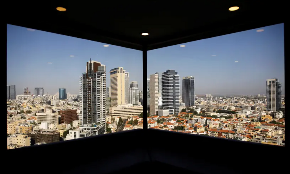 A general view of Tel Aviv's skyline is seen through a hotel window in Tel Aviv (photo credit: REUTERS)