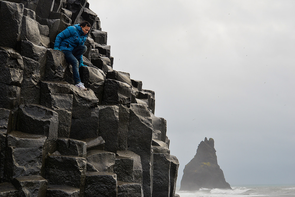 Jenson climb up high, with Reynisdrangar on its background. - Photo credited to Hybrid.
