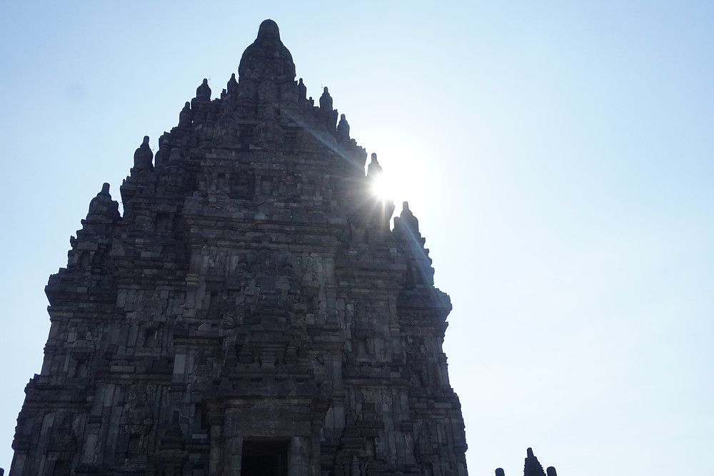 Sun hiding behind one of the Trimurti temple