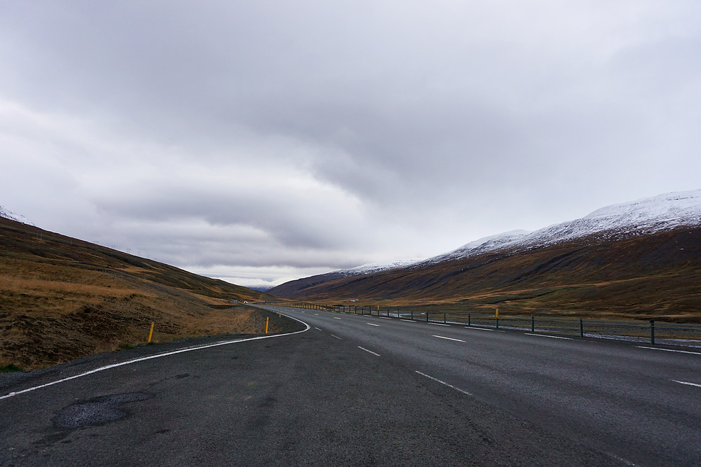 A long road that covered by snow capped mountain all around.