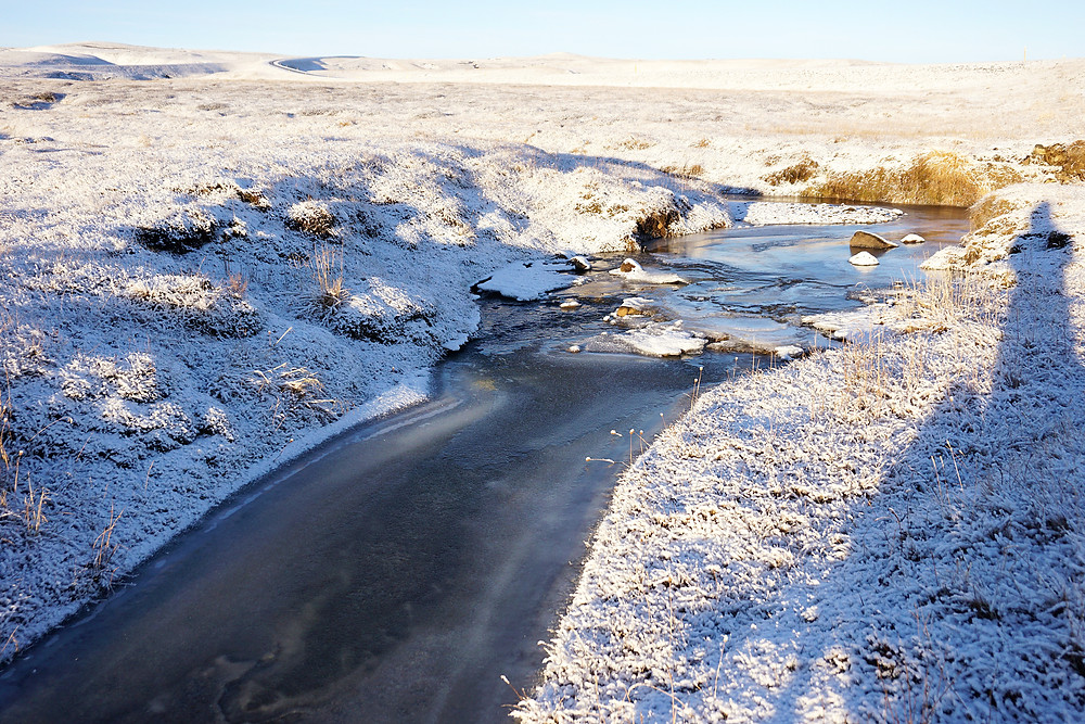 A frozen river, with water still flowing beneath it.