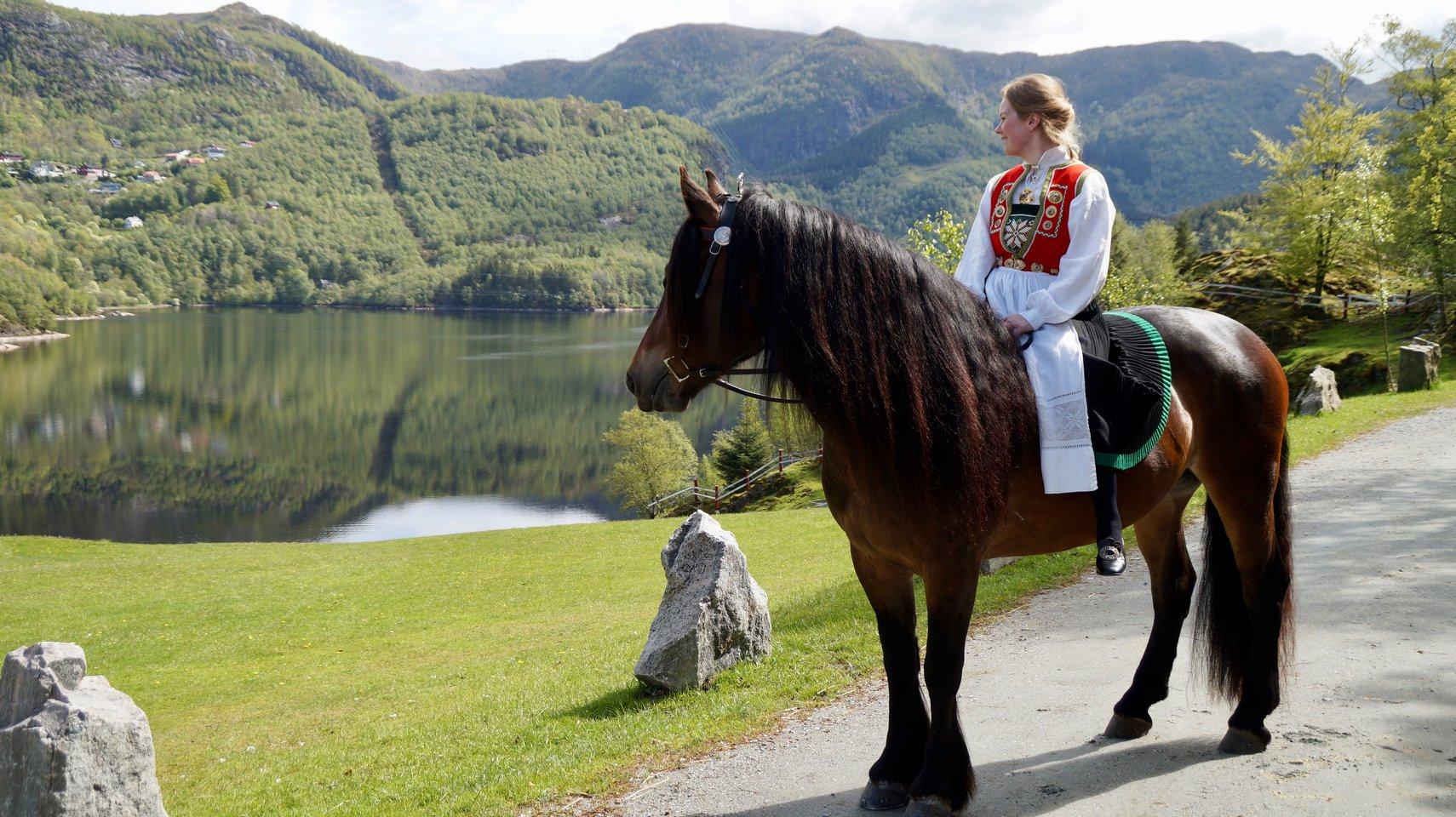 Jente rir på hest i Bergen