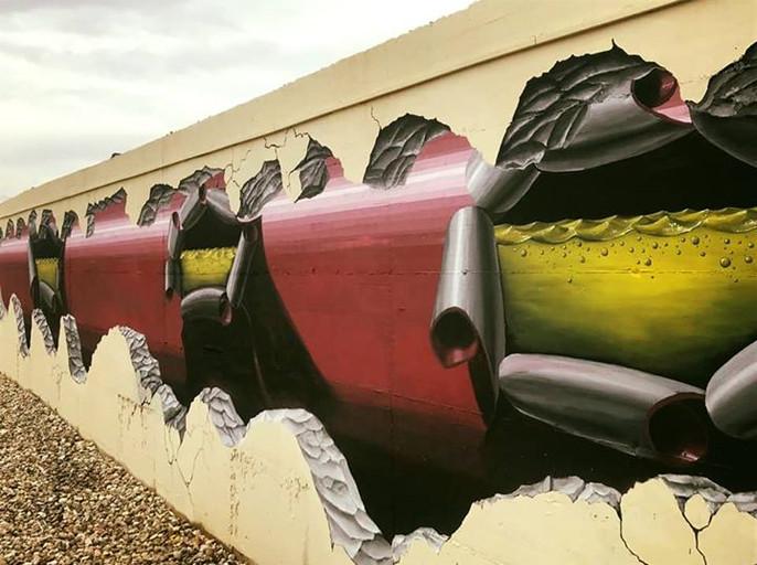 מיכל נפט עם קרעים מבעד לחור בקיר ציור קיר תלת מימדי בצבעי קיר, ספריי ואקריליק גודל: 15x2.5 מטר רמת פירוט: בינונית - גבוהה משך עבודה: שבוע מחיר: 5500 ש״ח