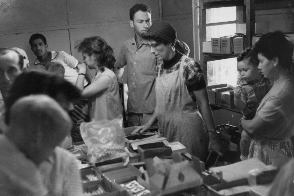 חברים עומדים בתור לקנות באספקה קטנה 1964