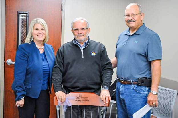 Cynthia Randazzo, Cass Community Health Foundation (CCHF) president, and Jim Person (right), newly elected CCHF Board of Directors Chairman, present Kenny Southwick (center) with a chair to recognize his service as CCHF Board of Directors chairman.