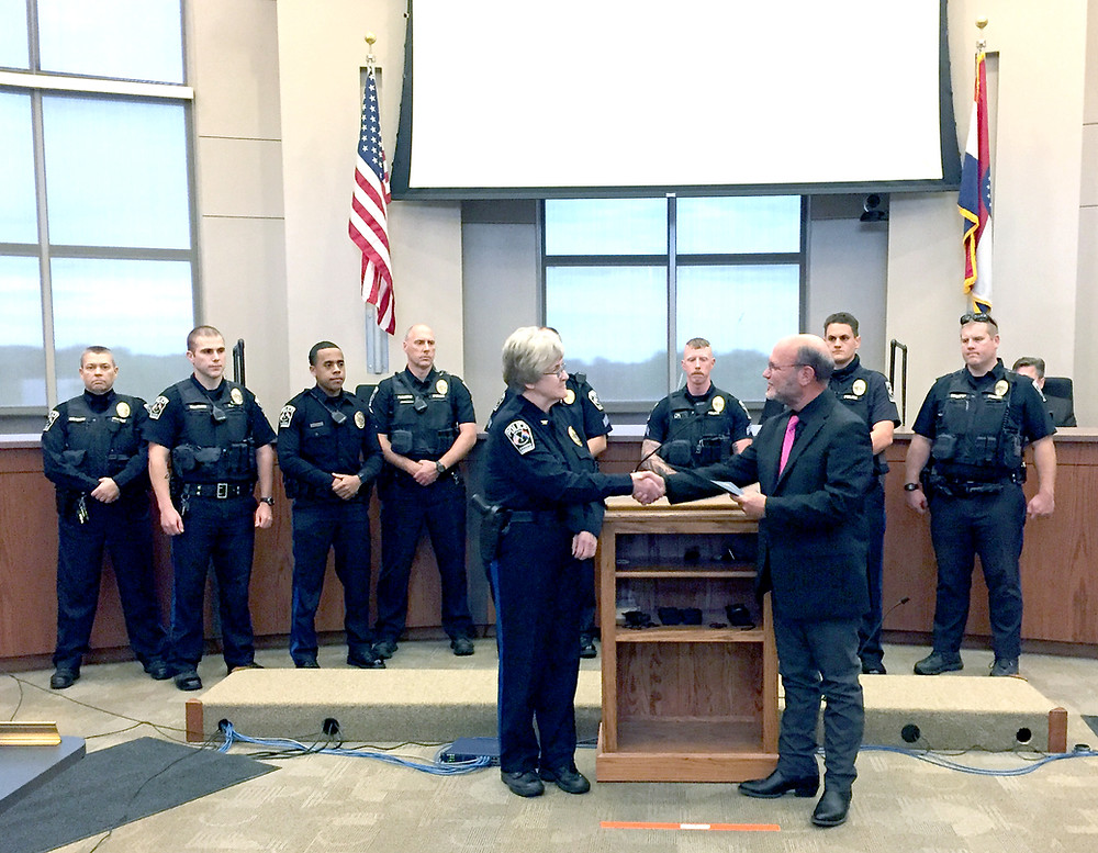 Raymore Police Chief Jan Zimmerman accepts a proclamation and congratulations from Mayor Pro Tem Dale Jacobson in recognition of National Police Week during Monday's City Council meeting. On-duty officers attended the ceremony.