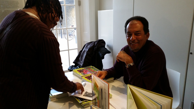 Hakim signing copies of African and Caribbean Communities in Britain, 2014