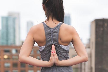 En kvinna står med sina händer synliga bakom sin rygg.