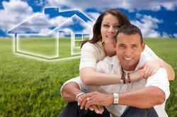 Hispanic-Couple-Sitting-in-Grass-Field-with-Ghosted-House-Behind-000033429884_La