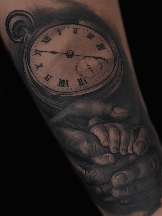 horloge et bébé mains sur l'avant-bras - tatouage noir et blanc - black house tattoo prague