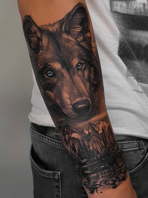 wolf and mountains on forearm - black and white tattoo - black house tattoo prague