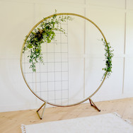 gold metal circle backdrop  125.  qty. 1 *price includes set up, does not include delivery *floral & metal grid not included