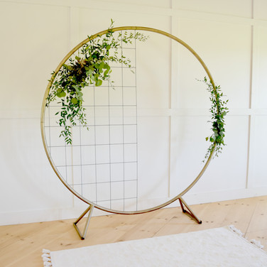 gold metal circle backdrop  125.  qty.1 *price includes set up, but not delivery *floral and metal grid not included