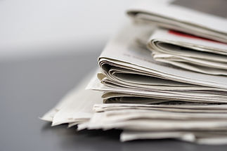 closeup-shot-several-newspapers-stacked-
