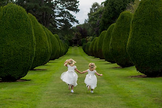 Flower girls holding hands running in pa
