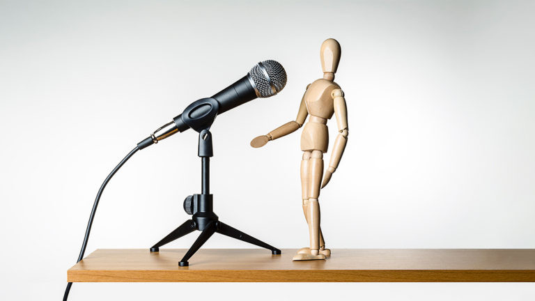 wooden figure on table in front of microphone