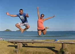 man and woman jumping over a bench at the beach