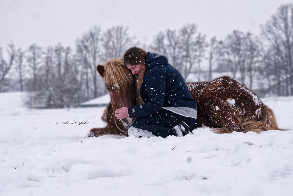 Jacky mit Isländer Nökkvi sitzend im Schnee