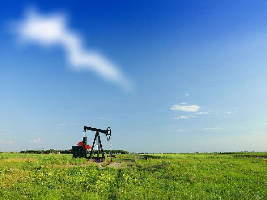 A pumpjack by a grassy field.jpg