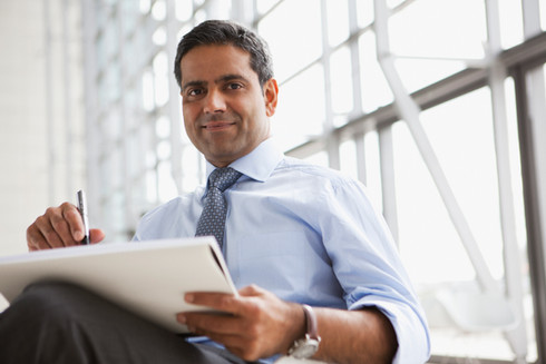 Businessman with pen and paper looking pleased