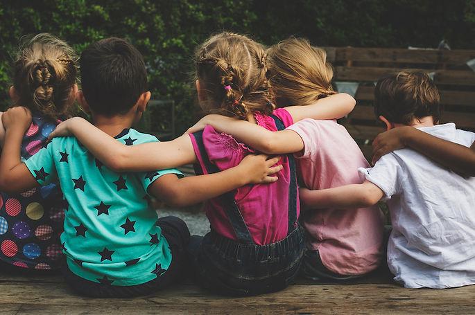 Group-of-children-sat-together-hugging.j
