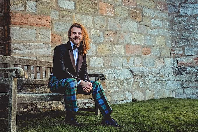 Man wearing tartan trews sitting on bench