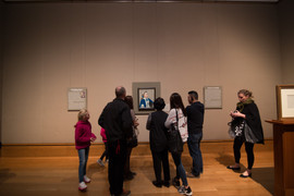 Getty Museum gathering around small art.