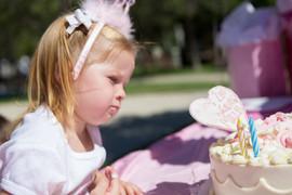 BIRTHDAY GIRL PONDERING HOW TO EAT CAKE.