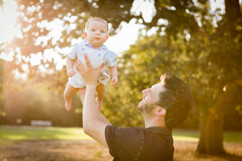 DAD HOLDING 3 MONTH OLD SON IN THE AIR.j