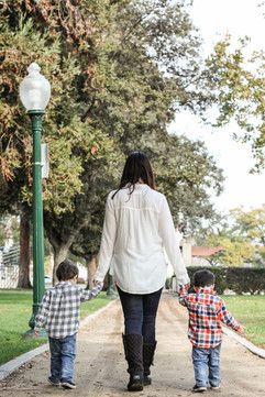 MOTHER WALKING IN PARK WITH TWINS IN A P