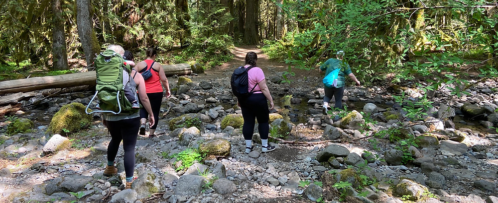 4 adults and one small child in frame backpack pick their way across a rocky stream crossing