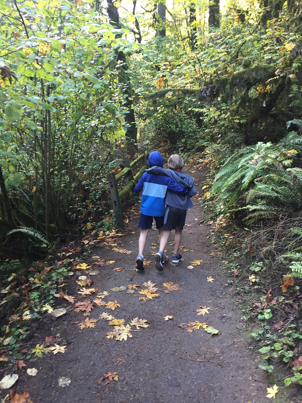 Two youth wearing shorts, sneakers, and sweatshirts walking down a dirt trail with arms around each other