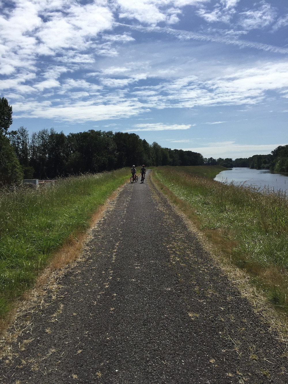 blue sky mottled with clouds over a gravel path next to a slough with two youth on bikes in the distance
